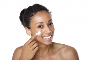 Attractive young woman applying cream on face