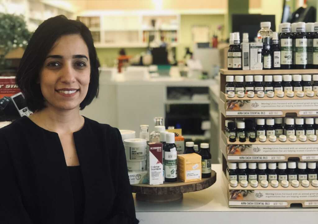 Pharmacist standing in front of counter with skin care products